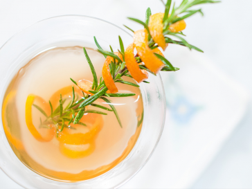 Aerial photograph of a martini with a fresh spring of rosemary as garnish with an orange peel wrapped around it.