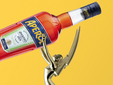 Emmy award holding bottle of oversized Aperol on. ayellow background