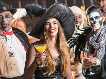 Woman dressed as a witch for Halloween holing a yellow martini in front of other poeple dressed up